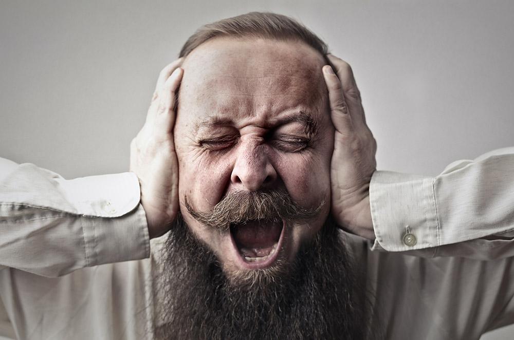 Ból ucha: Facet trzyma ręce na uszach i krzycy