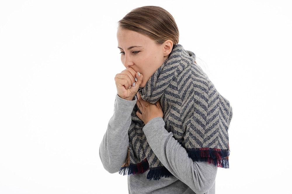 Kobieta ubrana w szary sweter i szalik kaszla