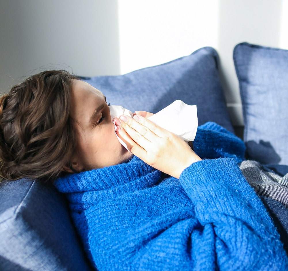 Flu: a woman is sick in bed, sneezing into a white napkin