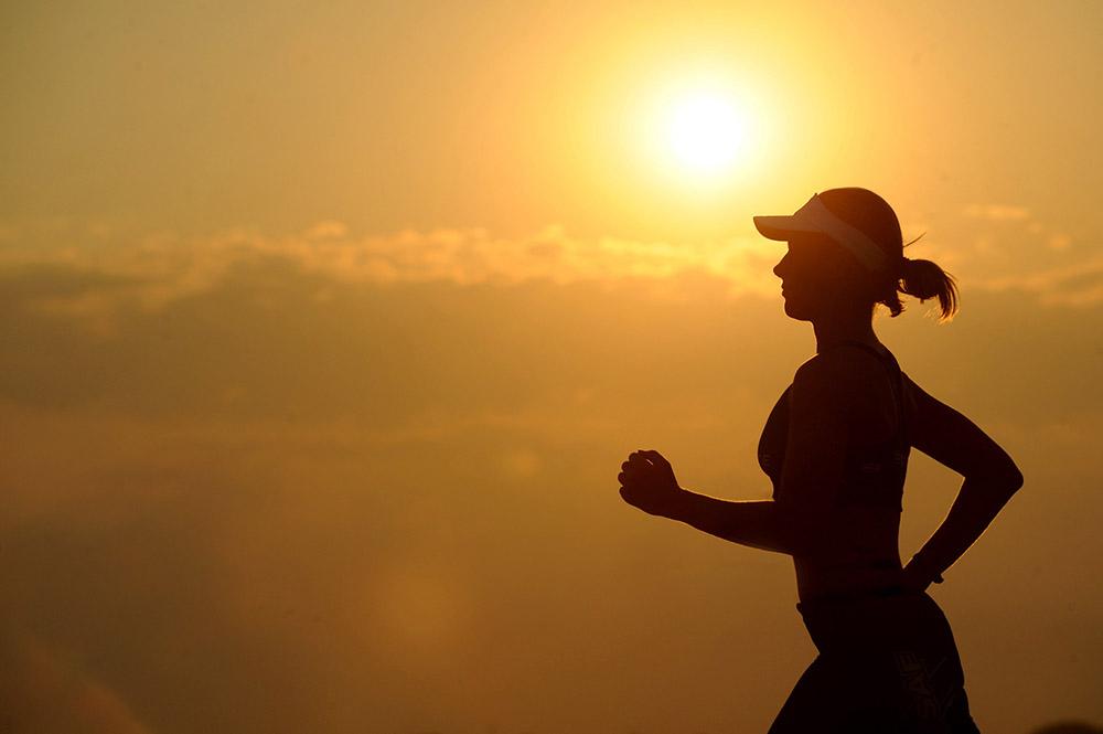Aby unikać choroby serca Pani na zdjęciu biegnie, na tle jest wschód słońca