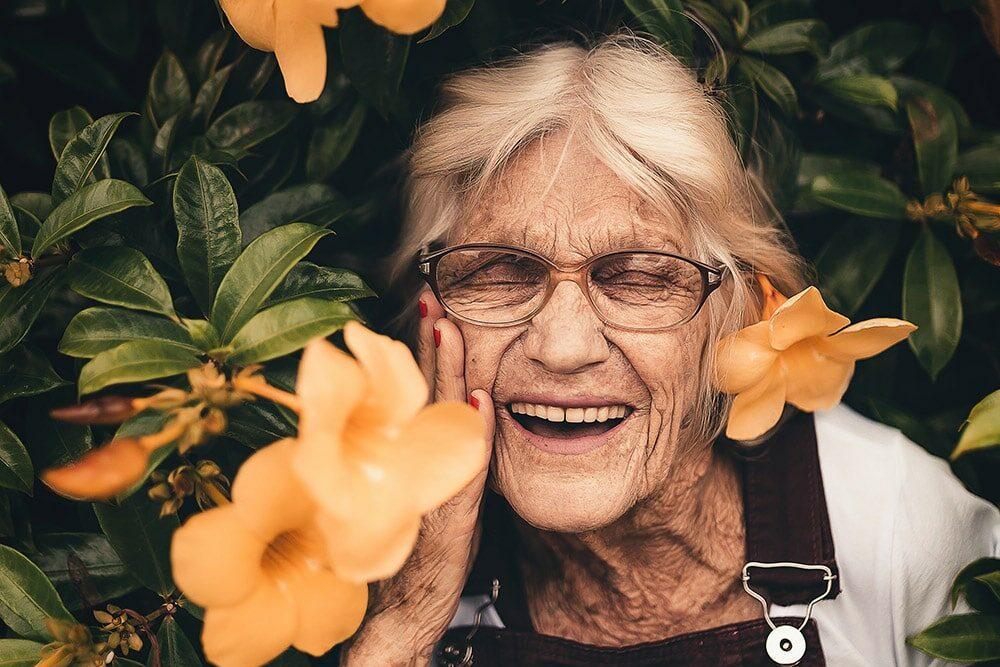 Menopauza: piękna PAni starsza uśmiecha się, na tle widnieją żółte kwiaty.