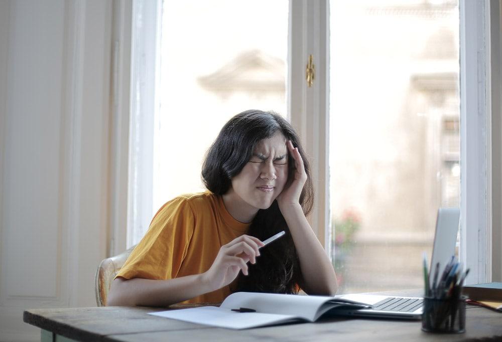 Migrena: Pani w żółtej koszule siedzi za biurkiem przy oknie trzyma lewą rękę u głowy, w prawej ręce ma długopis. Boli jej głowa. Na biurku leżą zeszyty.