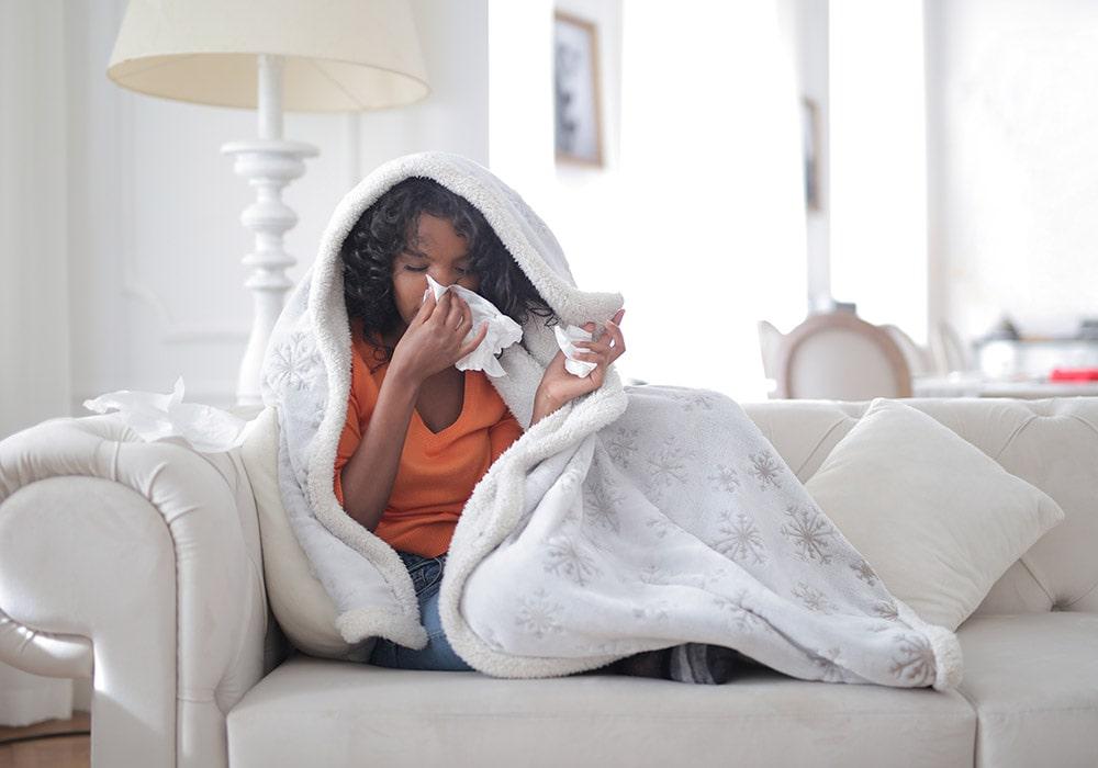 Dziewczyna siedząca na kanapie zawinięta w koc ma objawy Wirus zachodniego Nilu