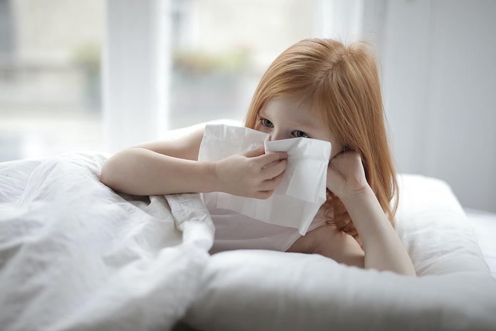 Choroby alergiczne: Dziewczynka z rudymi włosami leży na łóżku trzyma w ręce przed twarzą serwetkę, ona ma katar alergiczny.