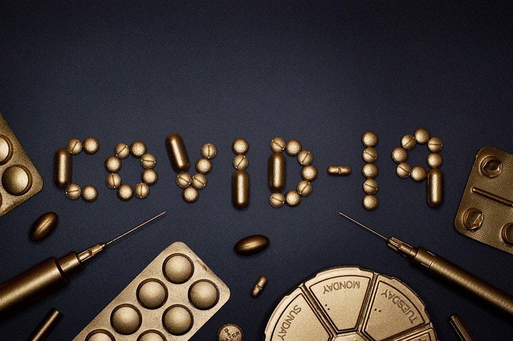 napis Covid-19 wokół którego leżą strzykawki, pigułki, leki itd.