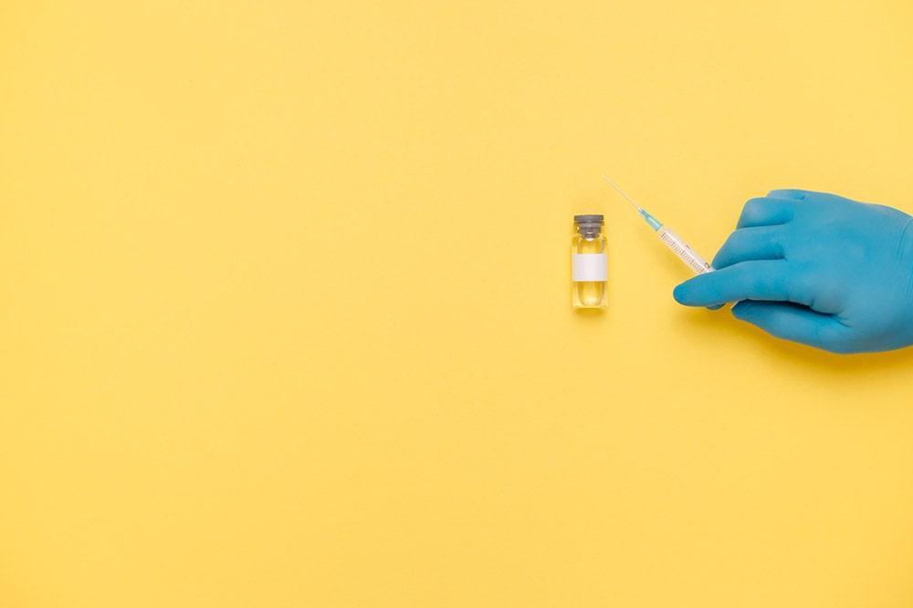 Insulina leży na żółtym stole, ręka w niebieskiej medycznej rękawiczce trzyma strzykawkę