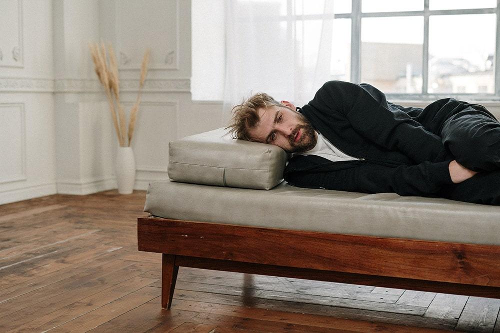 Zapalenie prostaty: Pan w czarnym ubraniu z zapaleniem prostaty leży na łóżku