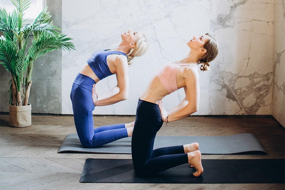 Two ladies are practicing yoga to prevent sciatica