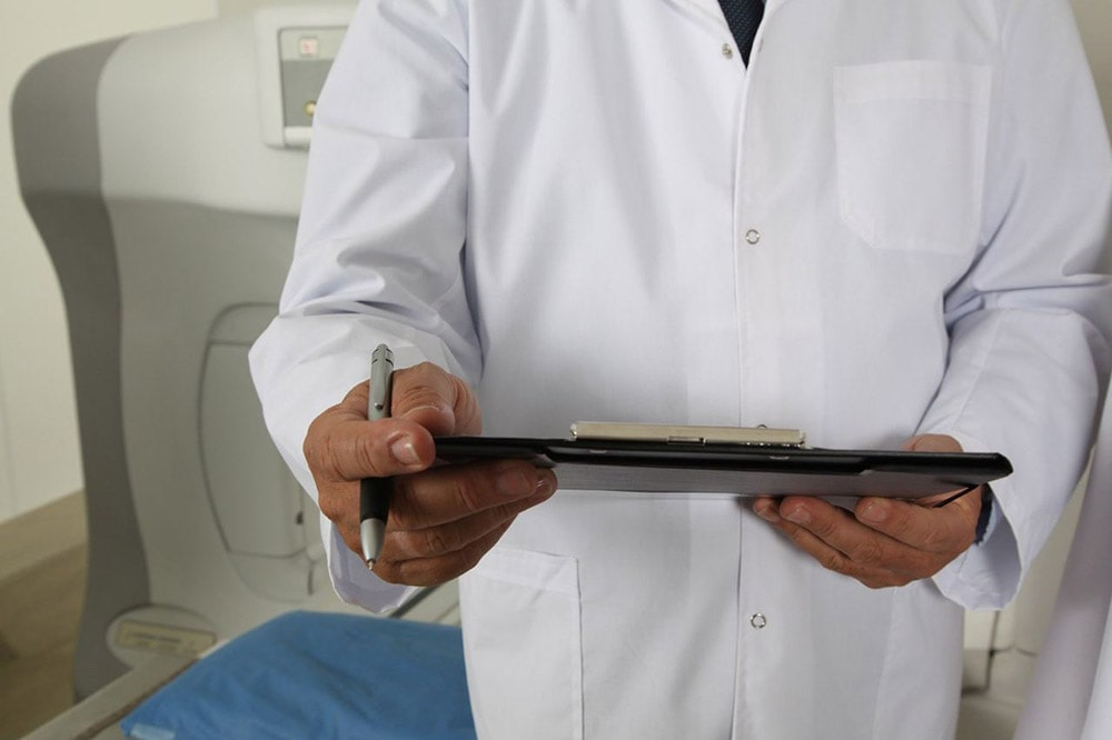 Gallstones: the doctor holds papers and a pen during the visit