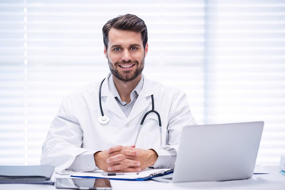 lekarz alergolog siedzi przed komputerem