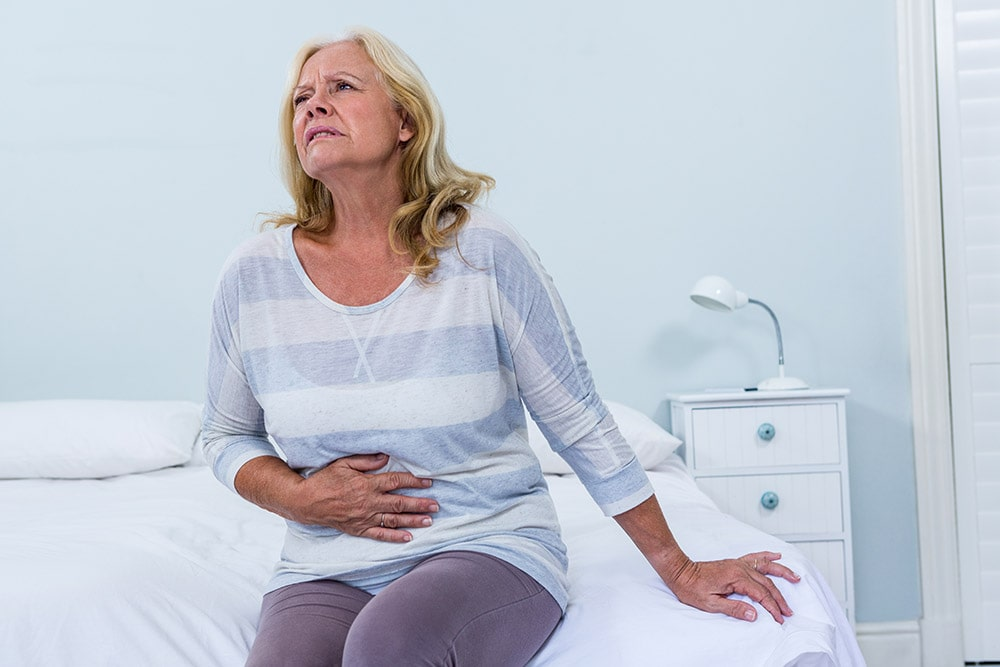The lady is sitting on the bed, has symptoms of food poisoning, has her hand on her stomach