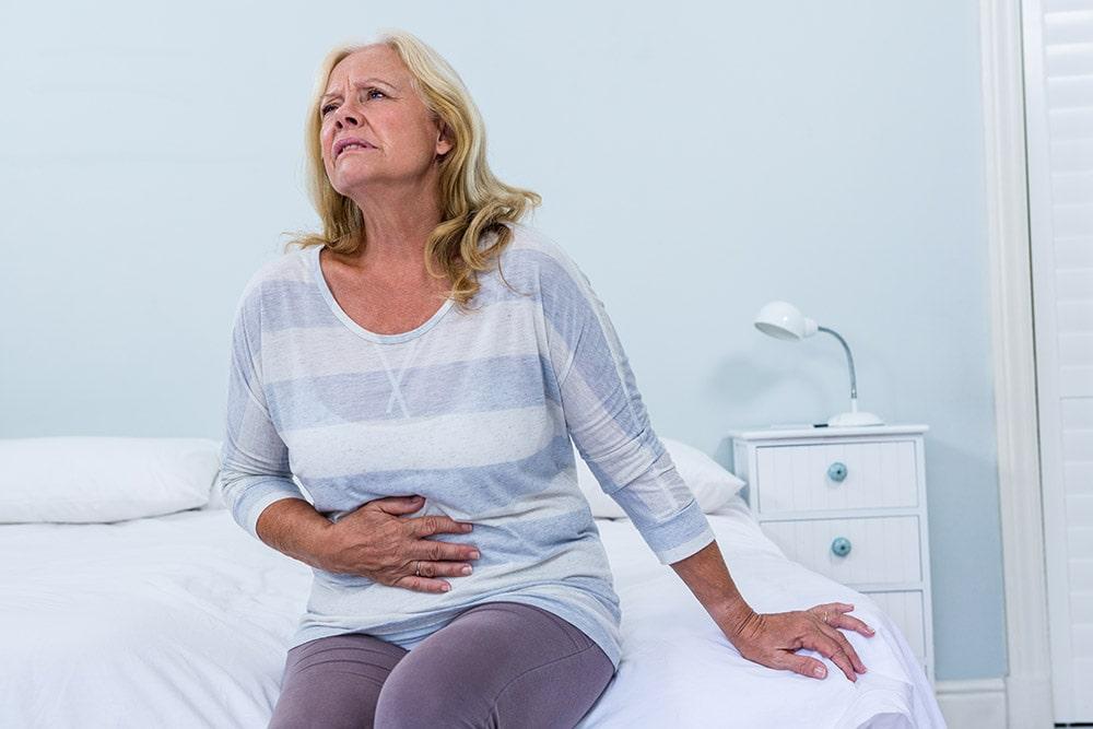 Pani siedzi na łóżku, ma objawy Zatrucie pokarmowe, trzyma rękę na brzuchu