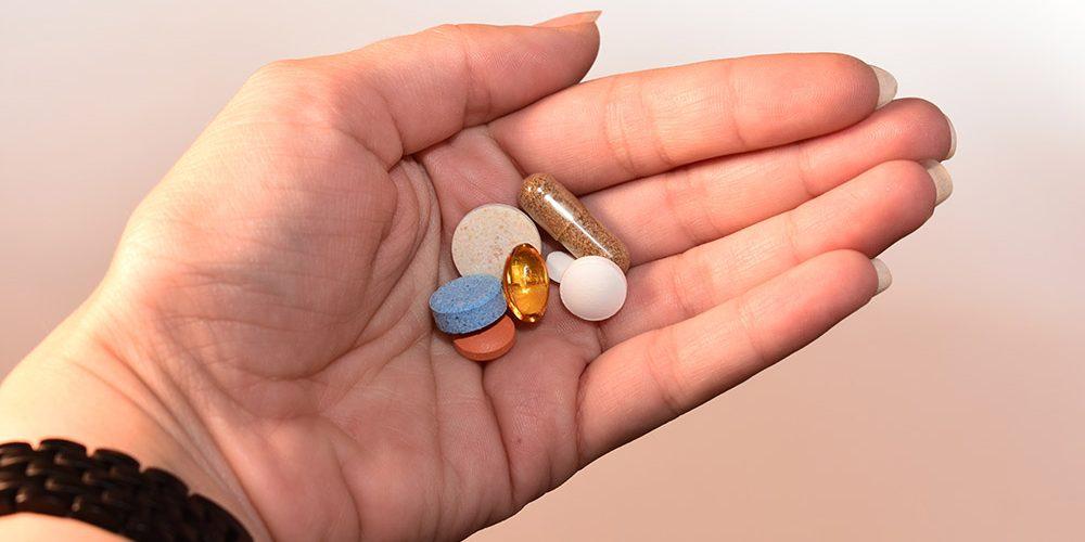 antykoncepcja hormonalna: w ręce są pigułki różnych kolorów