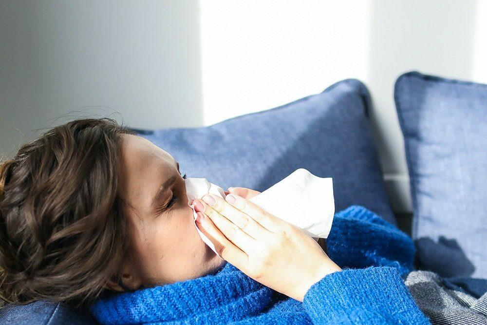 Grypa: kobieta leży w łóżku chora, kicha do białej serwetki
