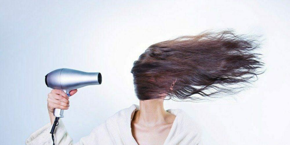 Kobieta suszy długi ciemne włosy suszarką, obrazek do artykułu na temat łysienia